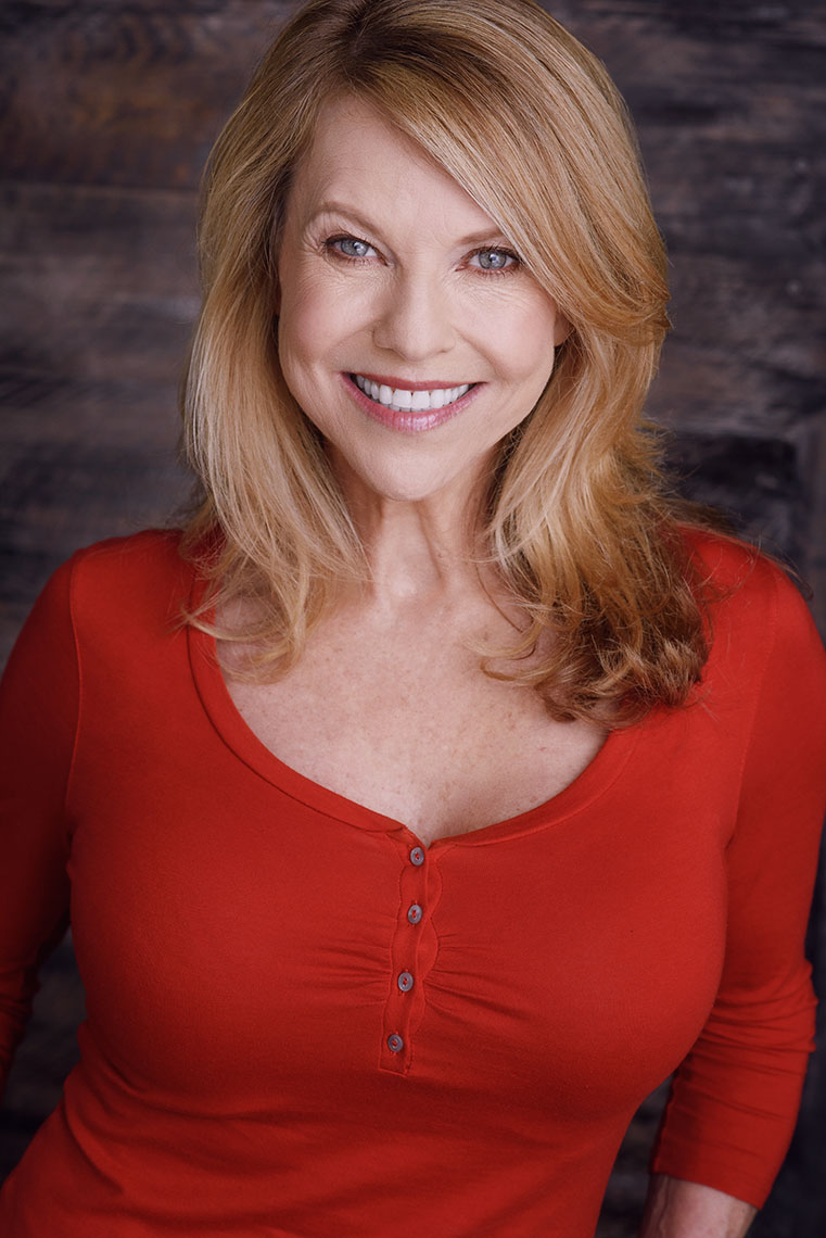 Actor Denise Riley  standouts in a bold red blouse with a wooden background and natural light .